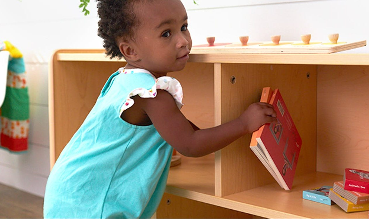 Young child putting away two books by Lovevery back on a shelf