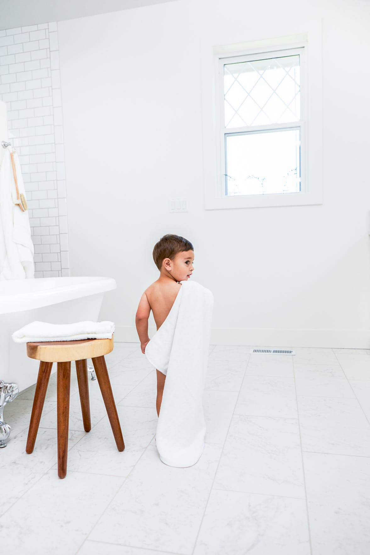Young child holding a towel walking to a bathtub