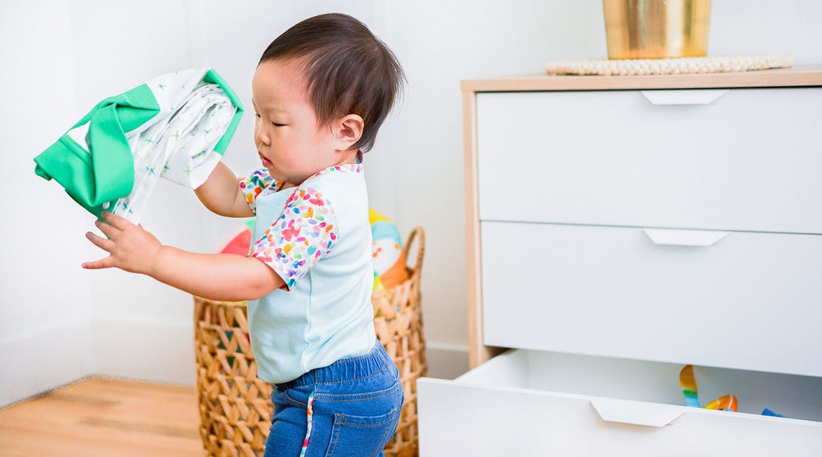 Toddler taking clothes out a dresser drawer