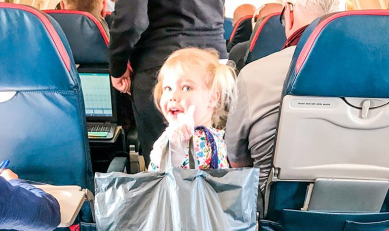 Young child walking down the aisle of an air plane holding a grey bag