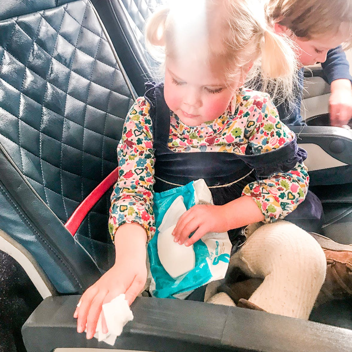 Toddler wiping down an air plane seat with wet wipes