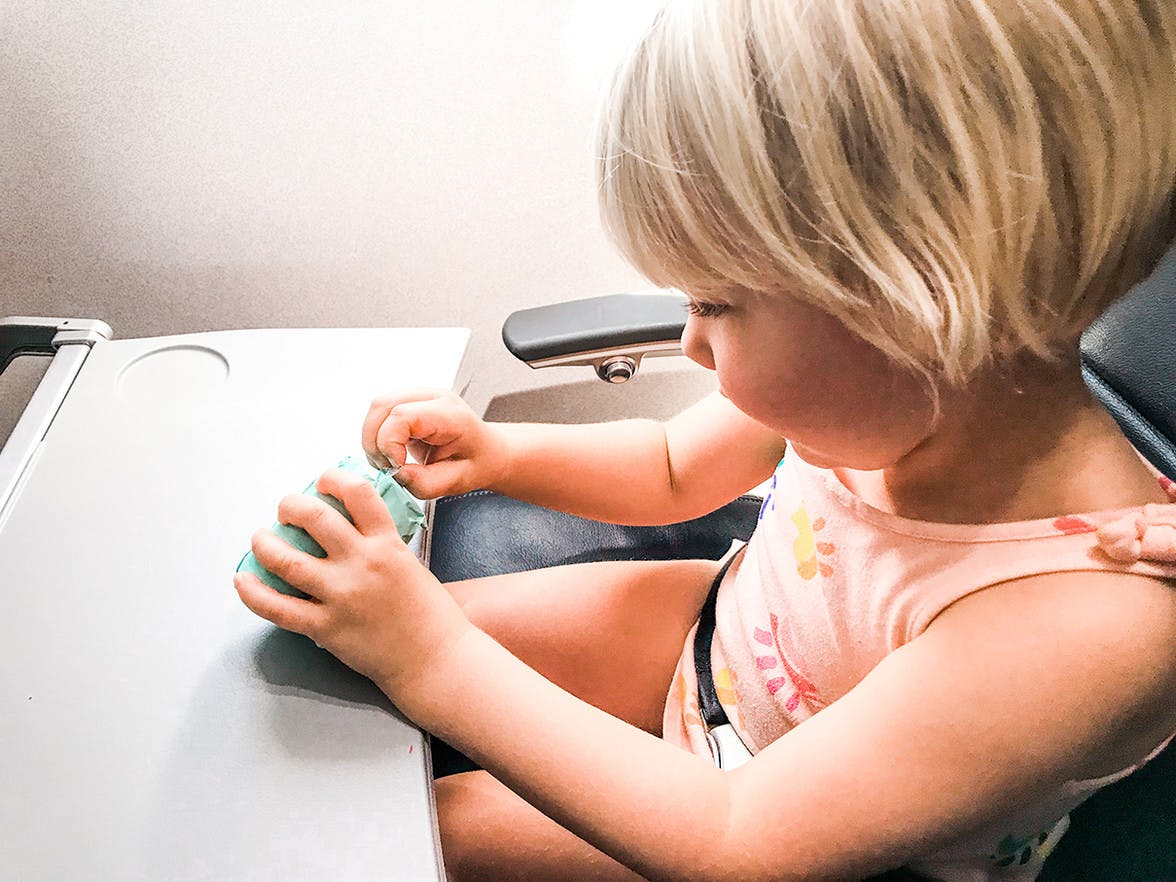 Child sitting in an air plane seat opening a toy