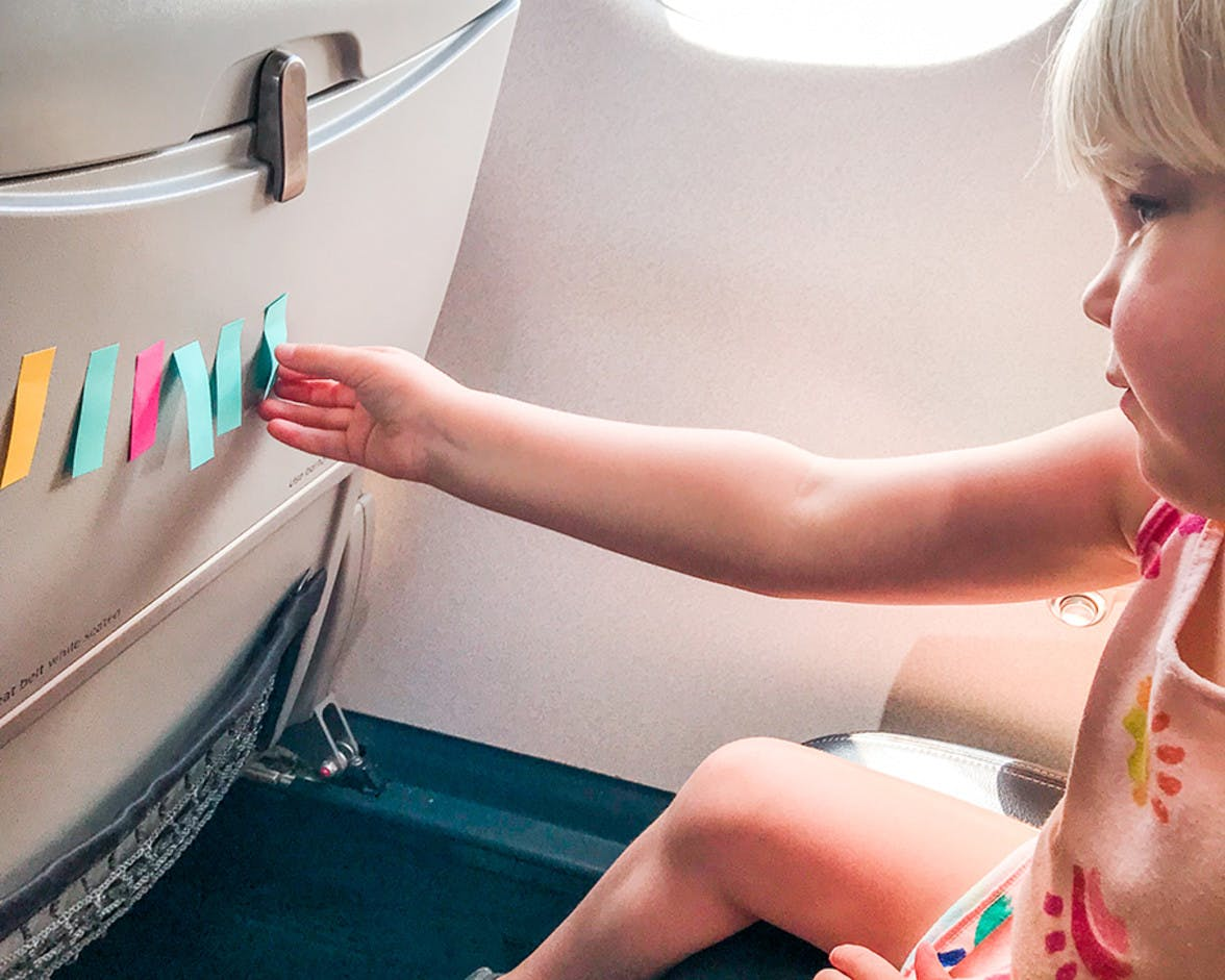 Child sitting in an air plane seat playing with post it notes
