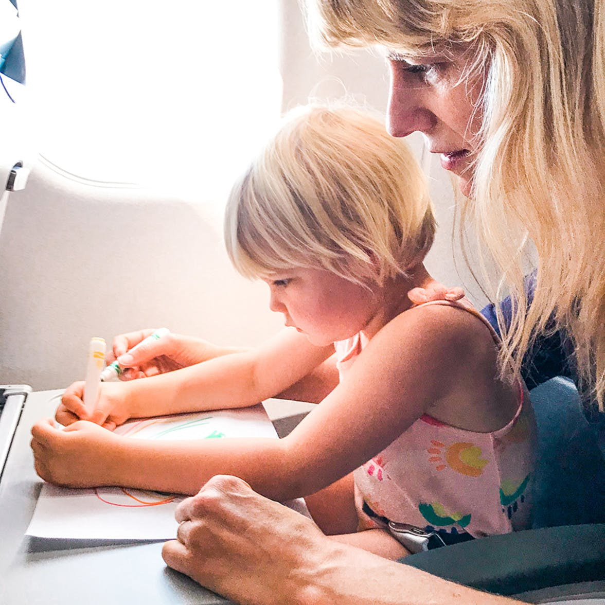 Child and mother sitting together on an air plane drawing on paper