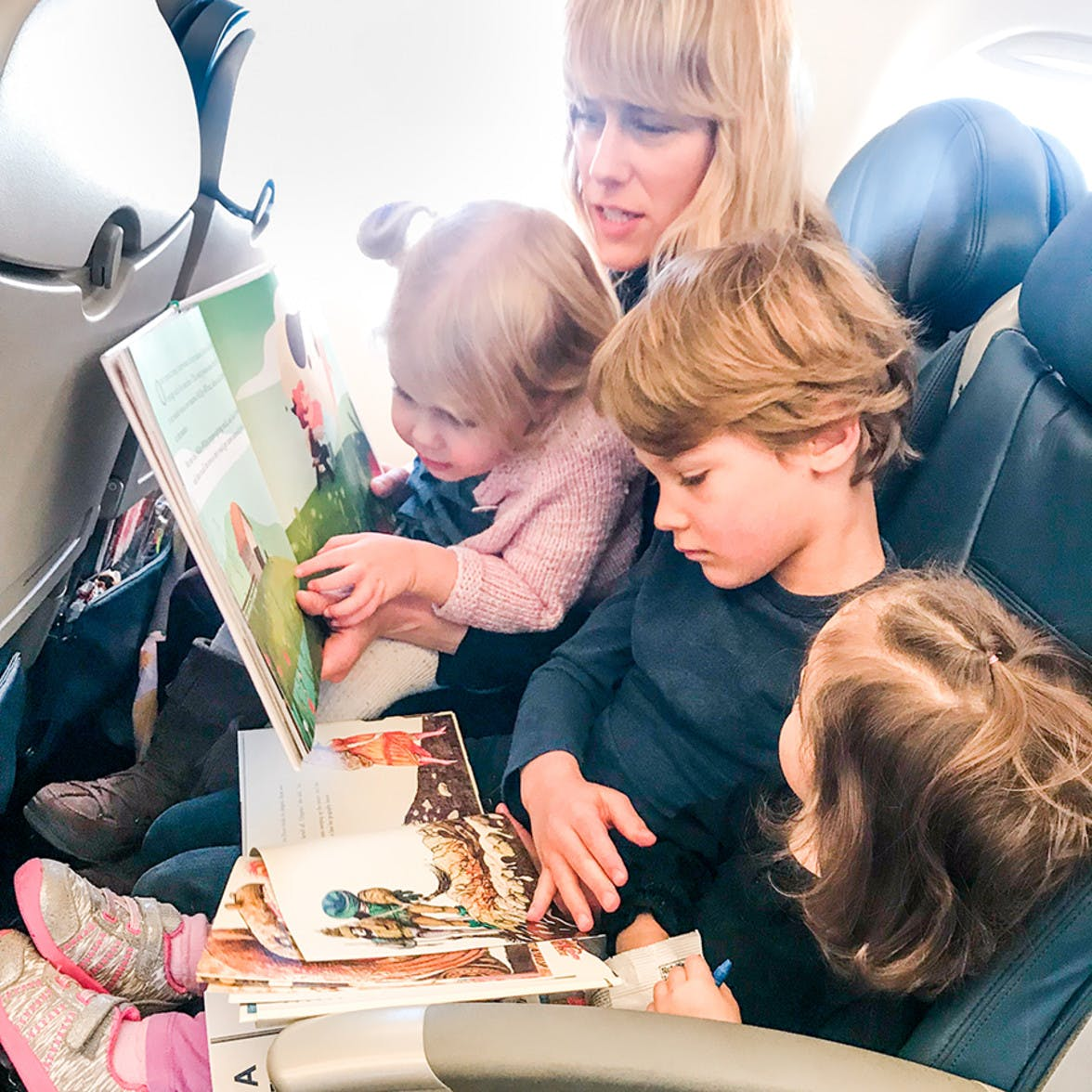 Three children and their mother sitting together on an airplane all reading books