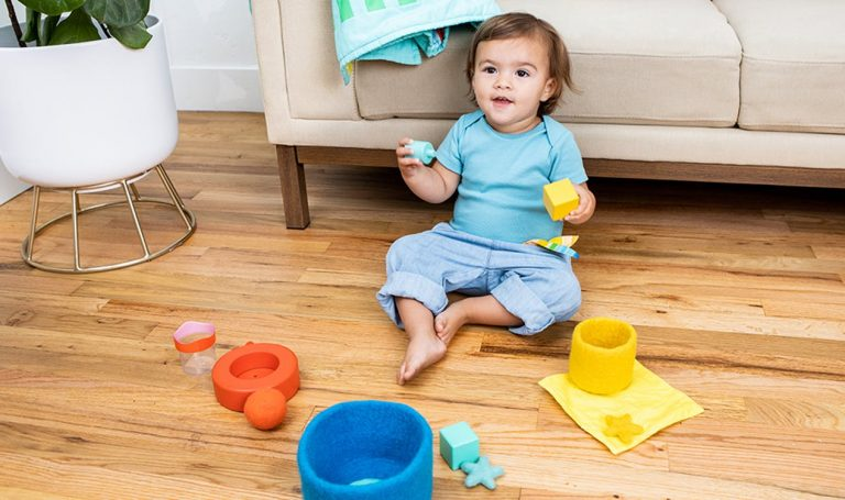 Toddler sorting different balls and containers by color