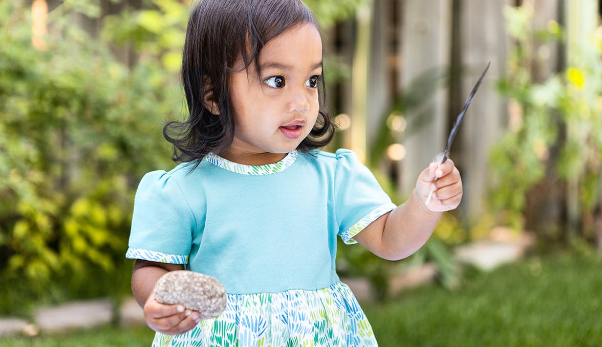 Toddler in a blue dress holding a feather and a rock