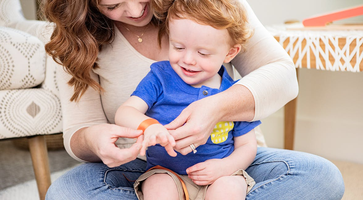 Woman holding a toddler in their lap and putting a piece of ribbon around their wrist