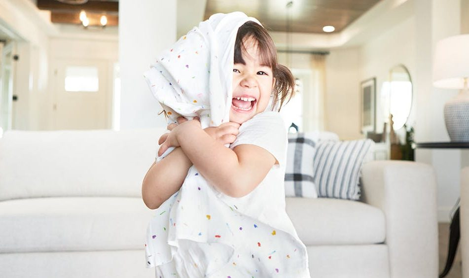 Toddler smiling and hugging an organic swaddle by Lovevery