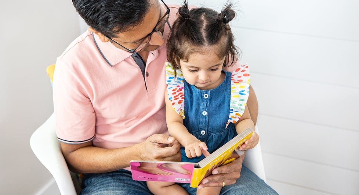 Toddler sitting on a man's lap looking at a book together