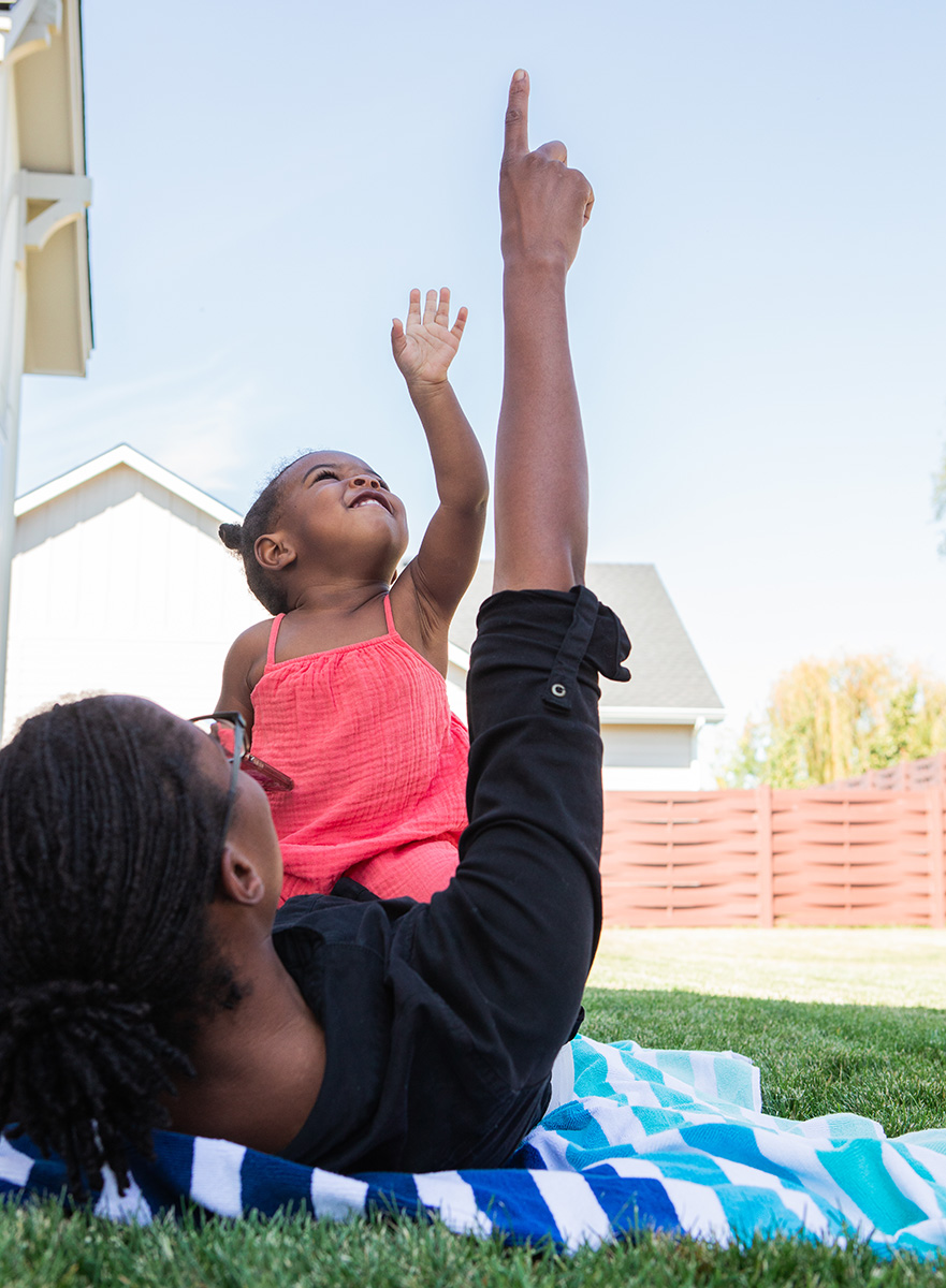 Toddler laying on a woman outside pointing up at the sky