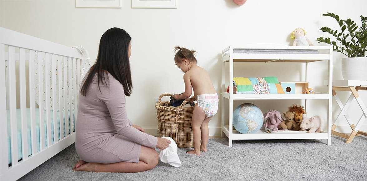 Young child putting clothes in a laundry hamper in their room