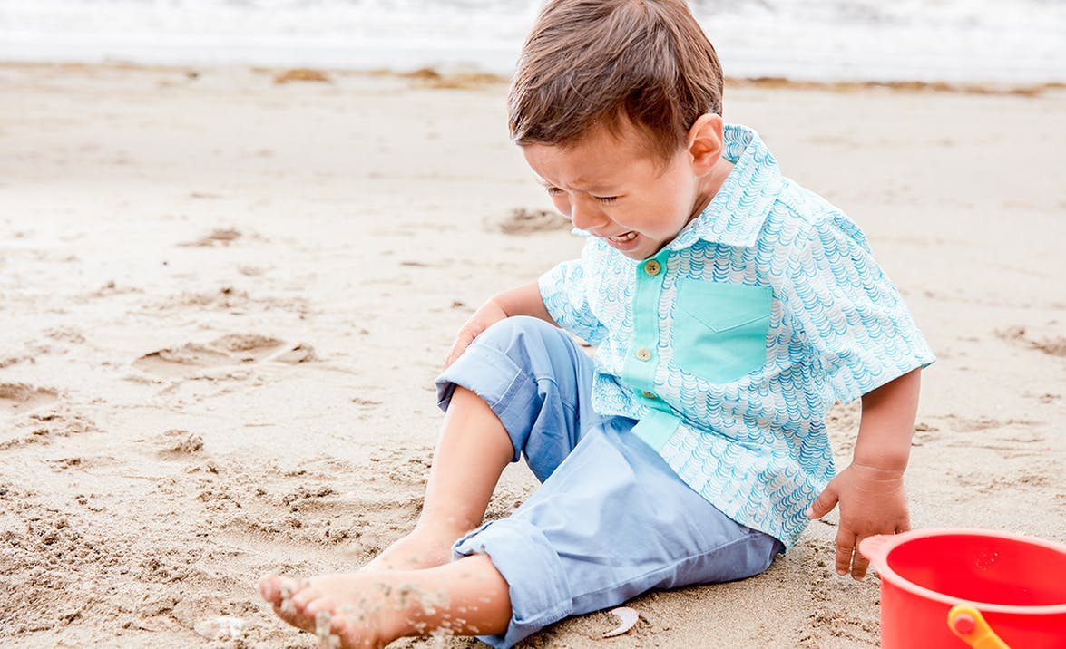 Young child crying and upset sitting in the sand at the beach