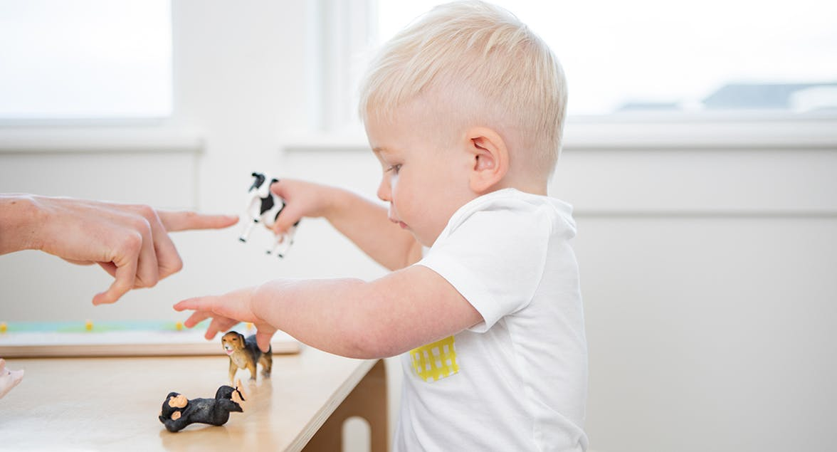 Toddler playing with animal figurines at a table