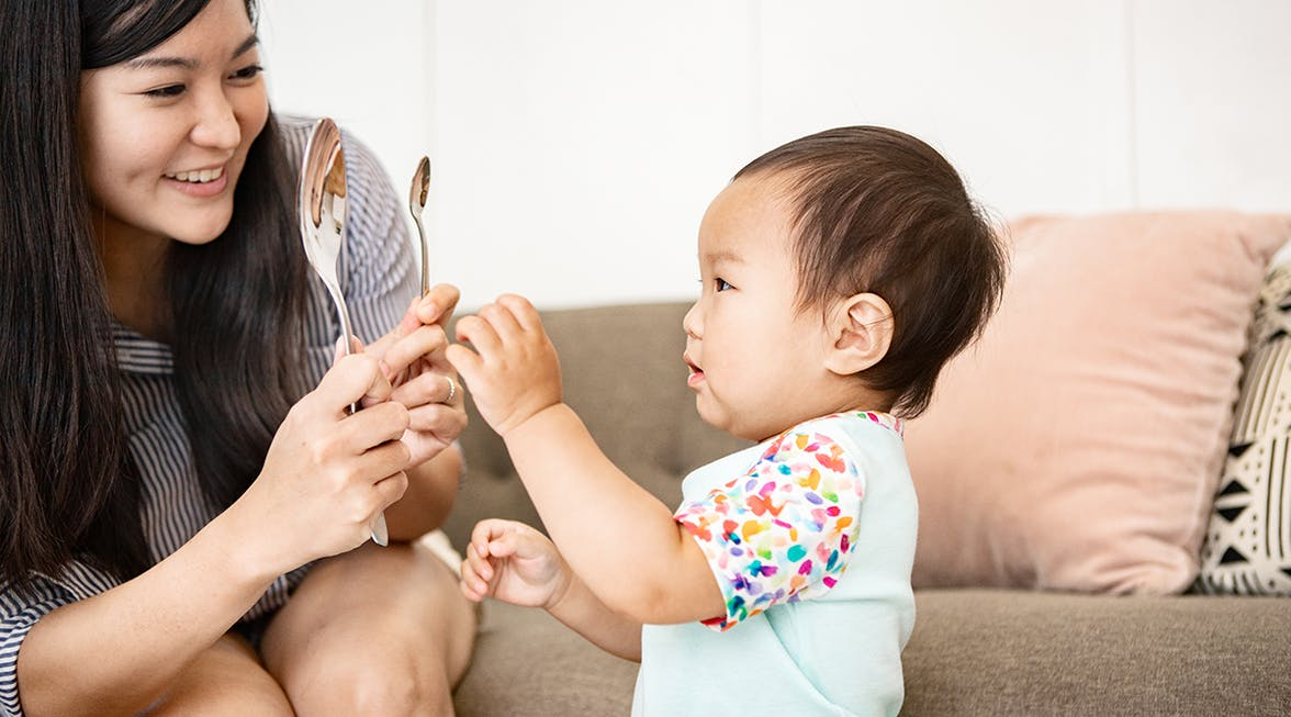 Woman holding two spoons in front of a baby