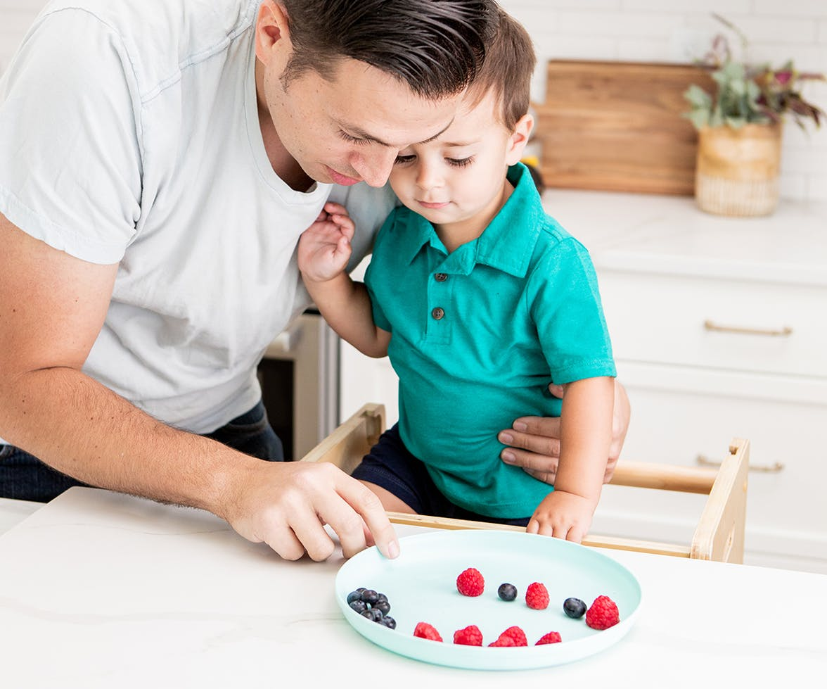 Father hugging a toddler while looking at a plate full of berries