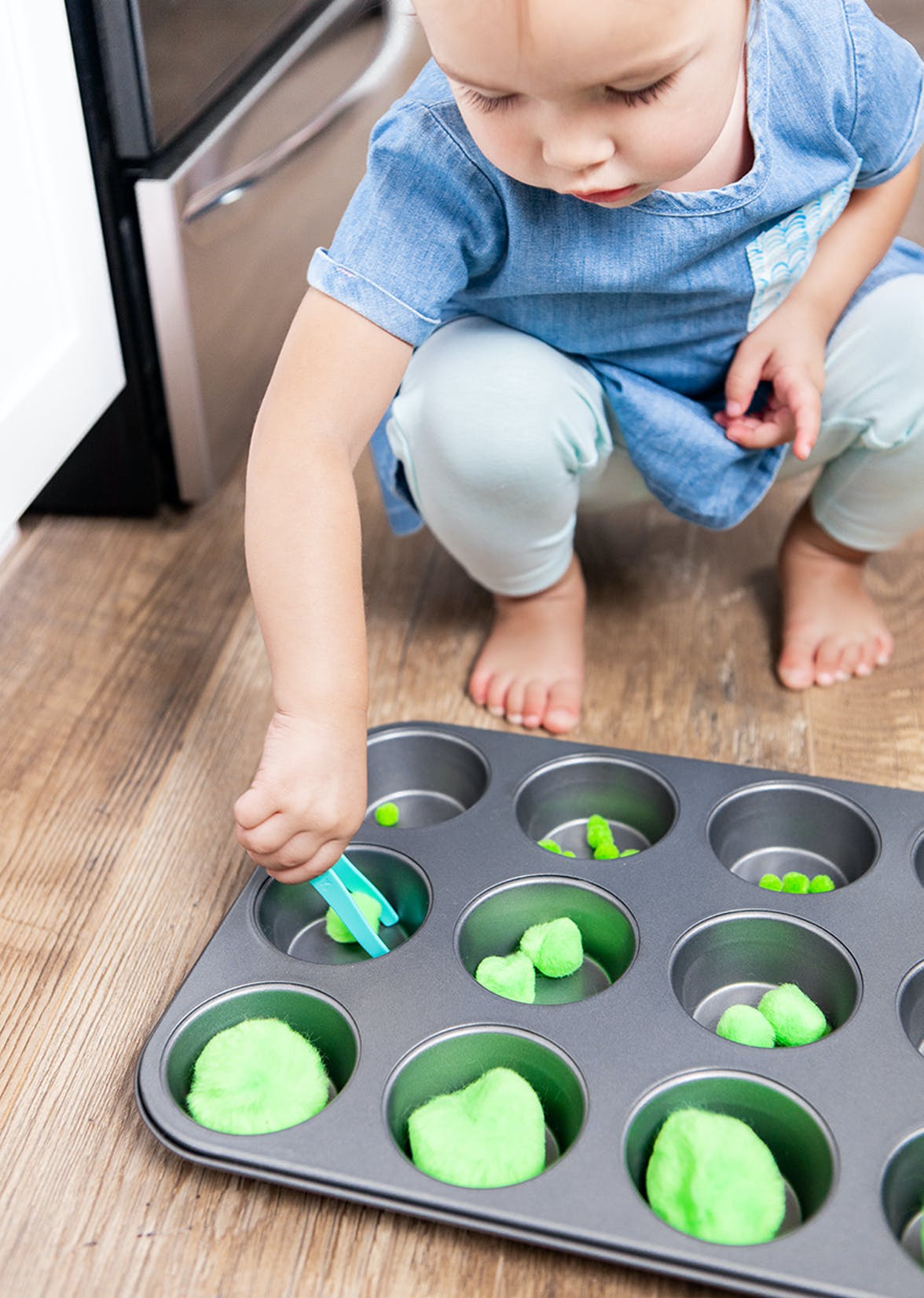 Young child playing with pom poms in a muffin tin