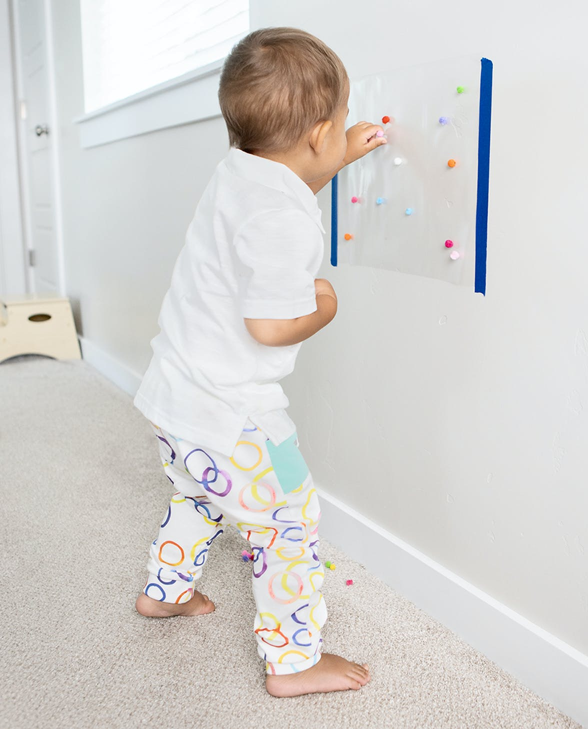 Young child putting pom poms on a sticky paper on the wall