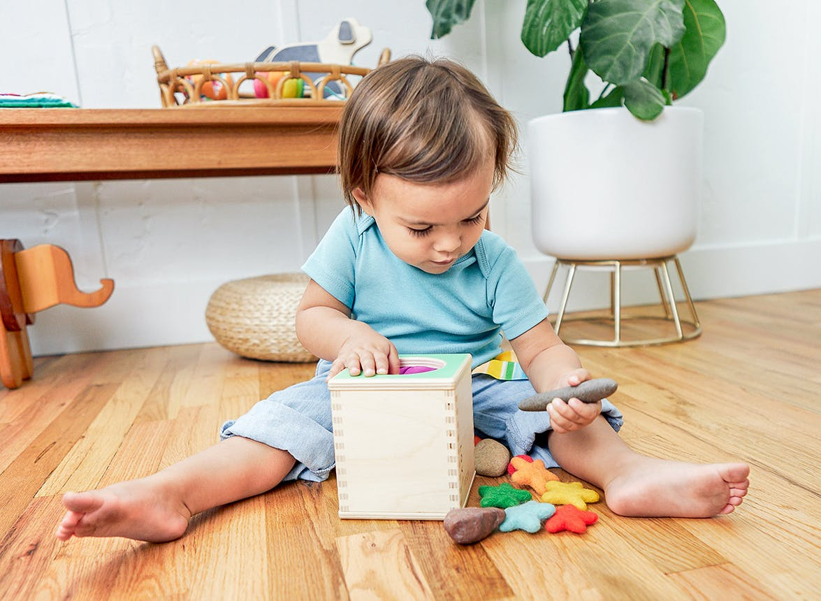 Young child pulling rocks and pom poms out of the Magic Tissue Box by Lovevery