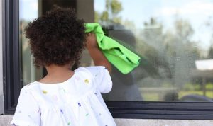 Young child holding a rag and cleaning a window