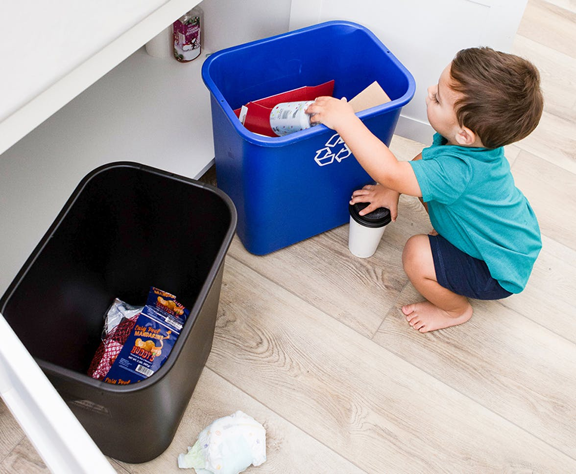 Young child putting a can into the recycling bin