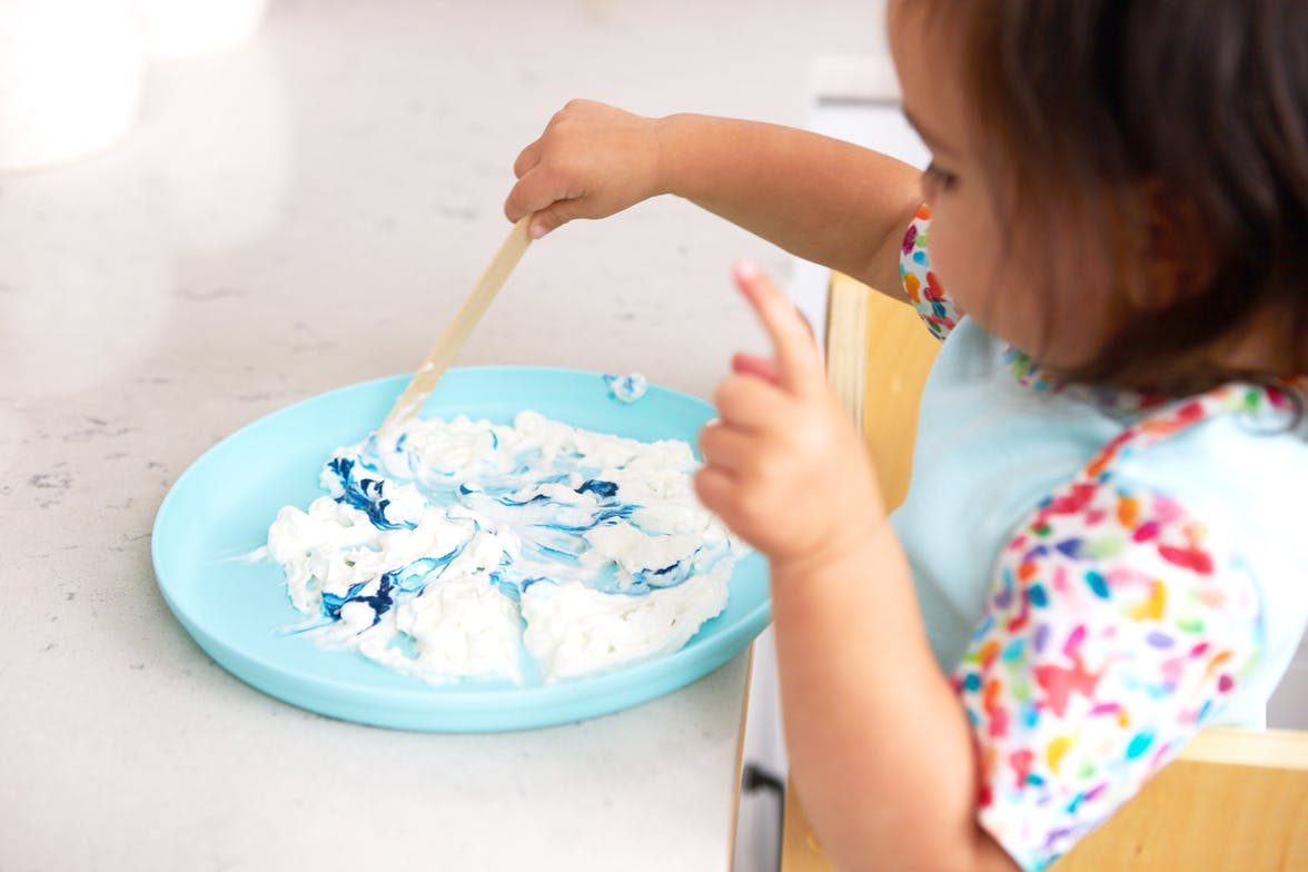 Toddler mixing shaving cream with blue food coloring at a kitchen counter
