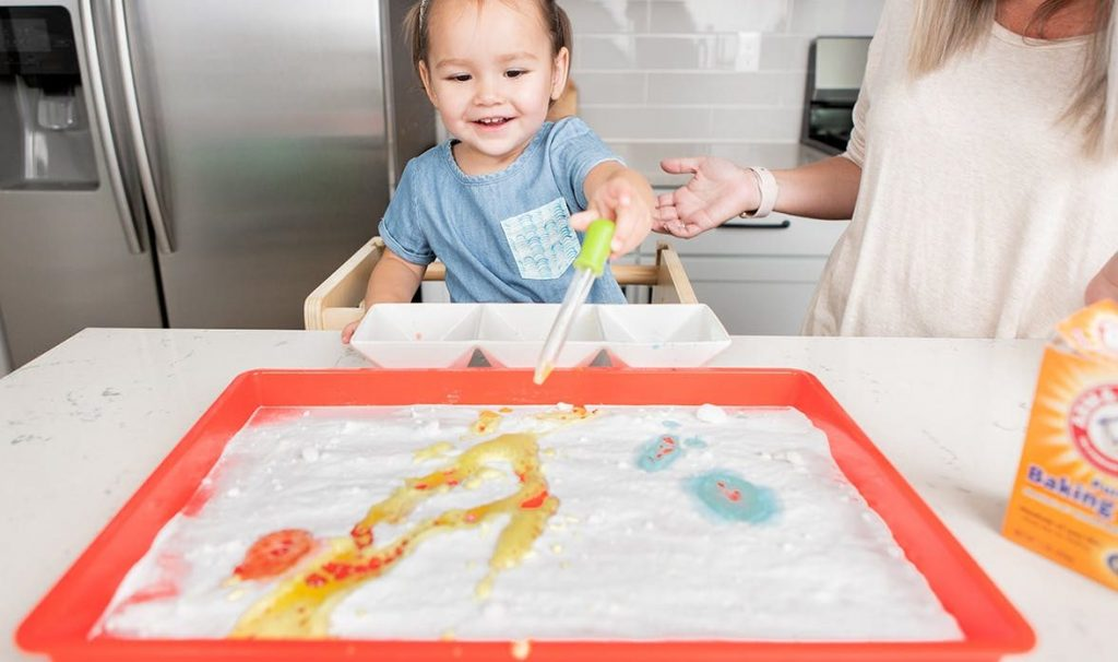 Child doing a DIY STEM activity with baking soda, food coloring, and water.