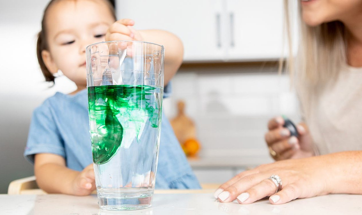Toddler stirring green food coloring into a glass of water