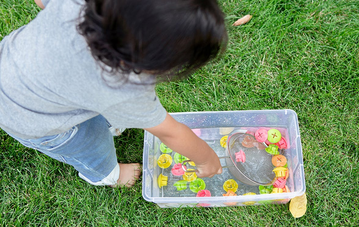 Toddler scooping out buttons from water on the grass