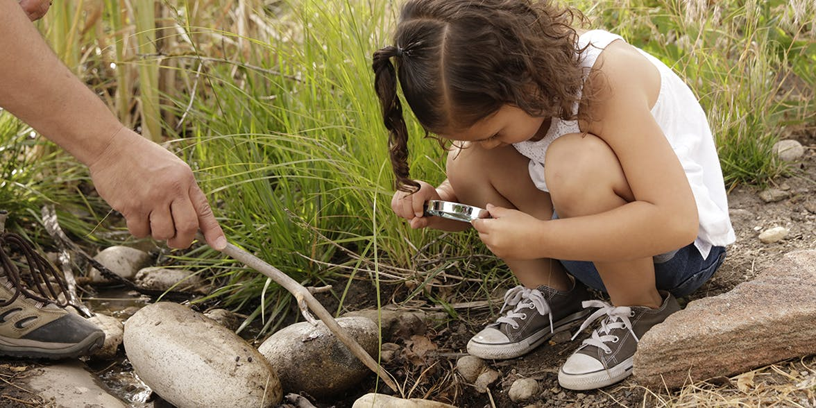 Young child looking through a magnifying glass at some rocks while sitting outside.