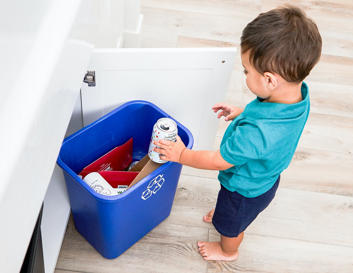 Young child placing a can in a recycling bin.