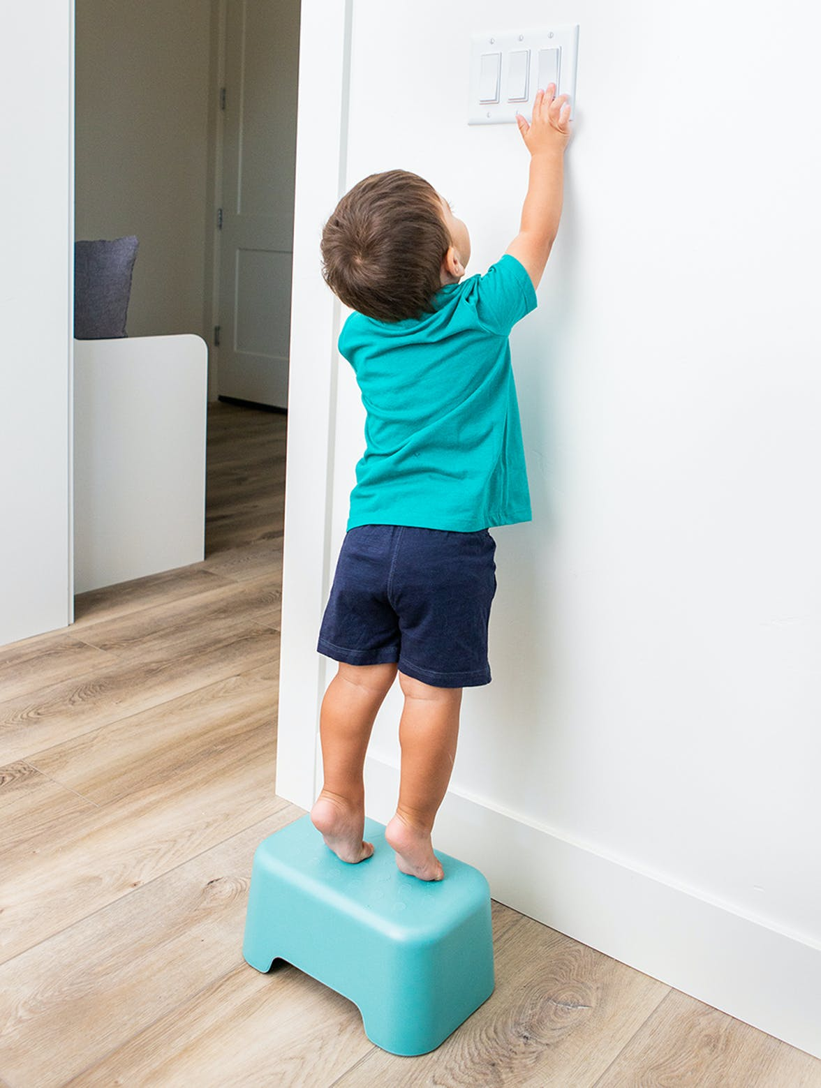 Young child standing on a stool flipping a light switch.