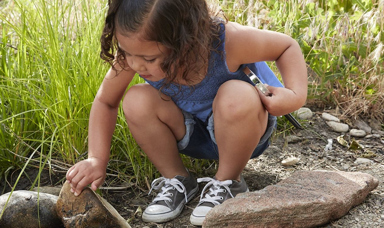 Young child holding a magnifying glass while looking at a rock outside.