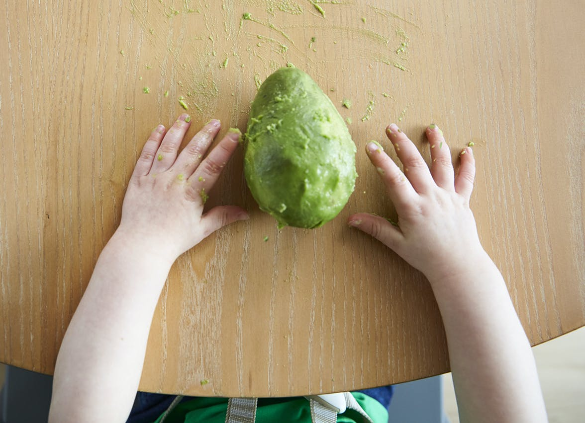 A toddler's hands with a peeled avocado between them