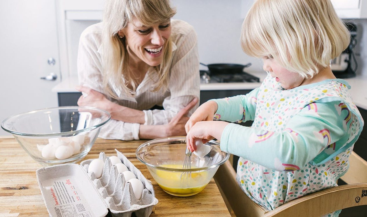 Toddler mixing a cracked egg into a mixing bowl in the kitchen