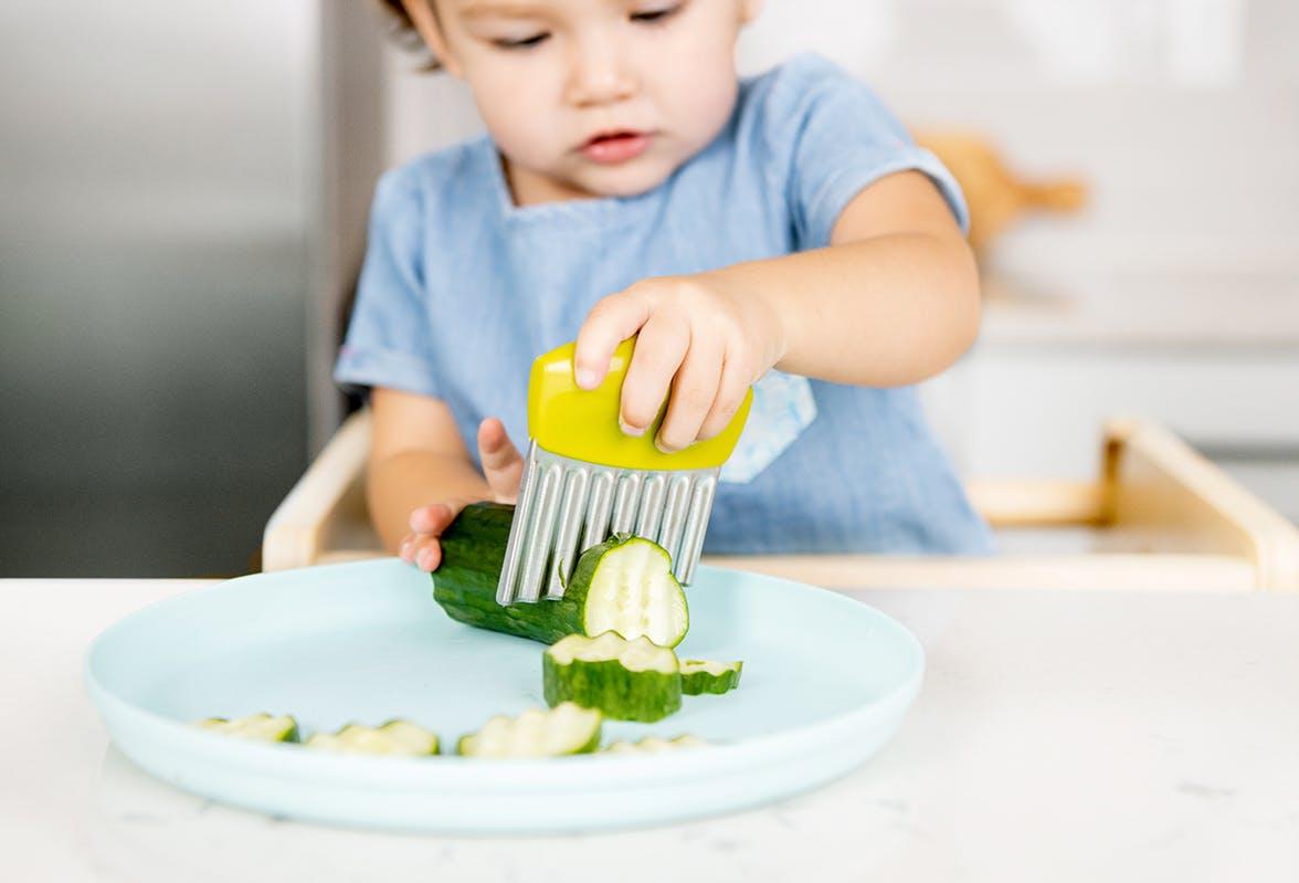 Toddler cutting up a cucumber