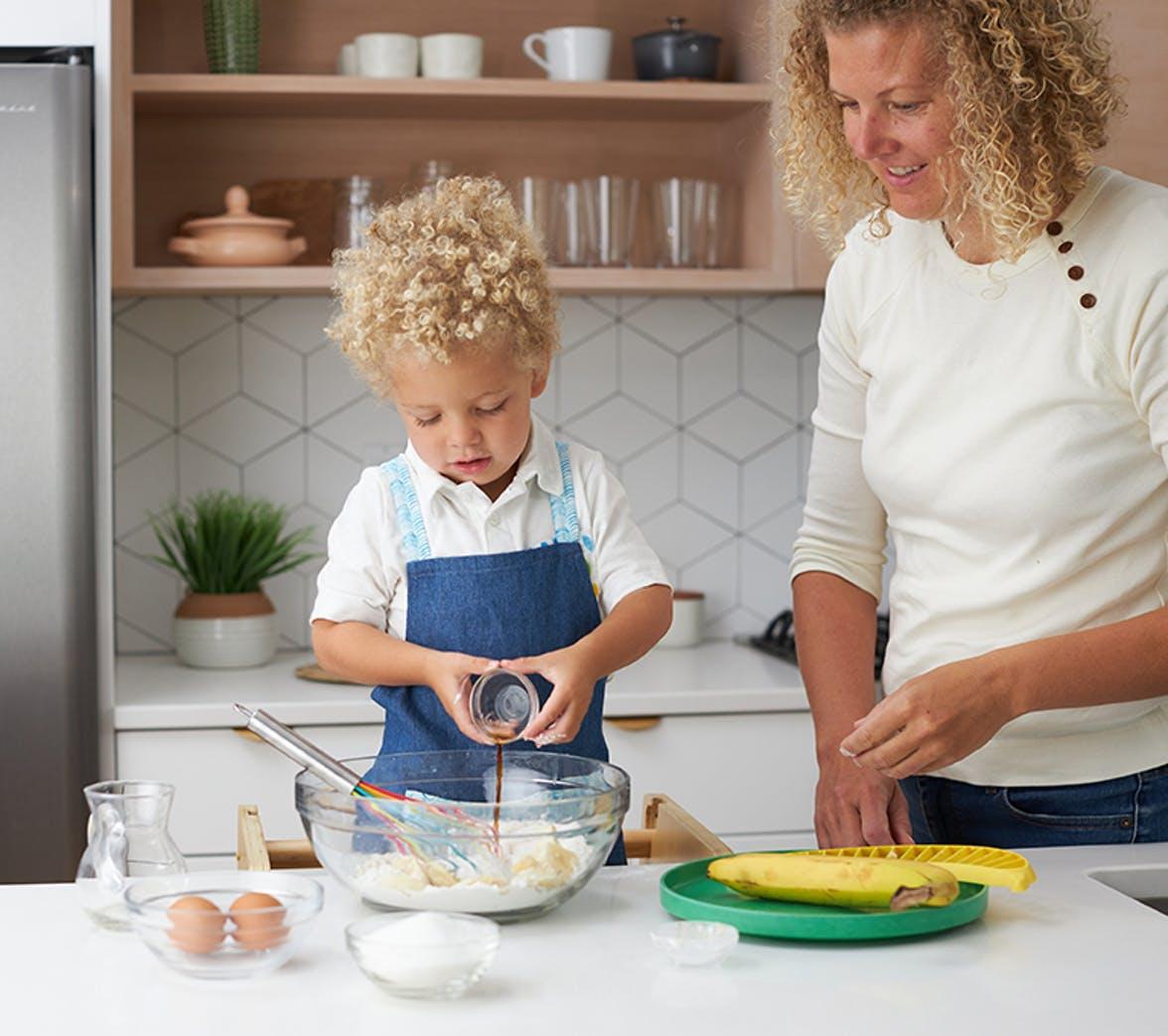 Toddler pouring vanilla into a mixing bowl