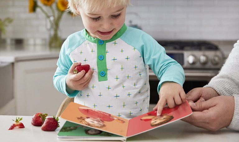 Toddler holding a strawberry and looking at a book by Lovevery