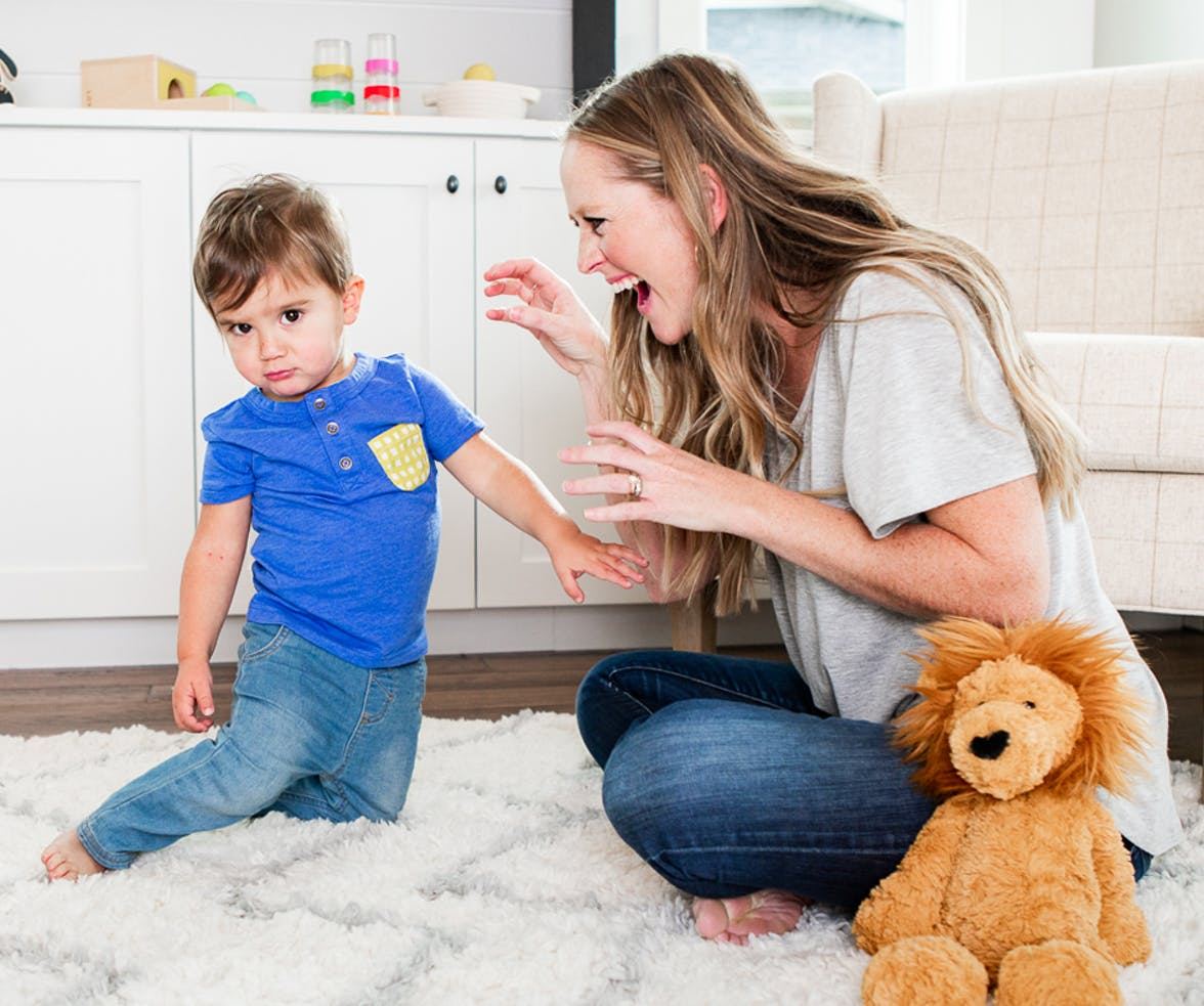 Woman roaring like a lion to a toddler next to a lion stuffed animal