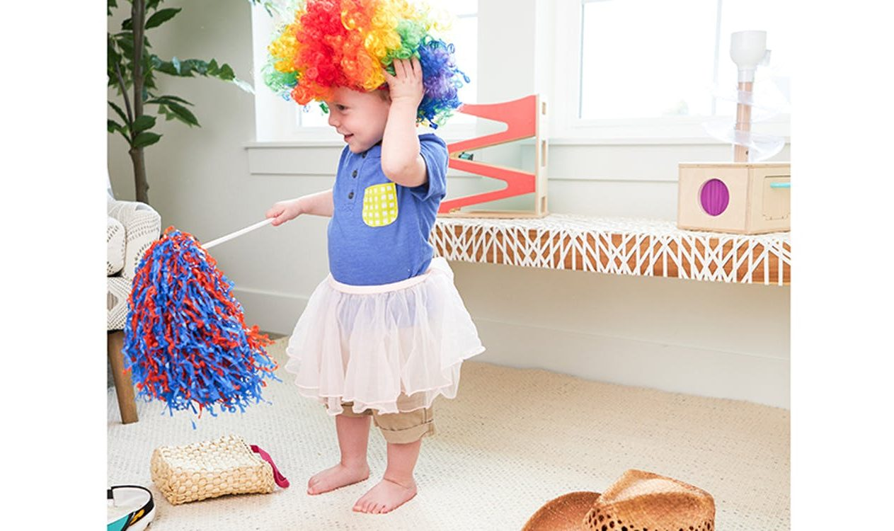 Toddler playing dress up with a clown wig, skirt, and pom pom surrounded by items by Lovevery