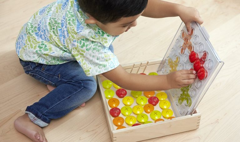 Toddler playing with the Drop and Match Dot Catcher by Lovevery