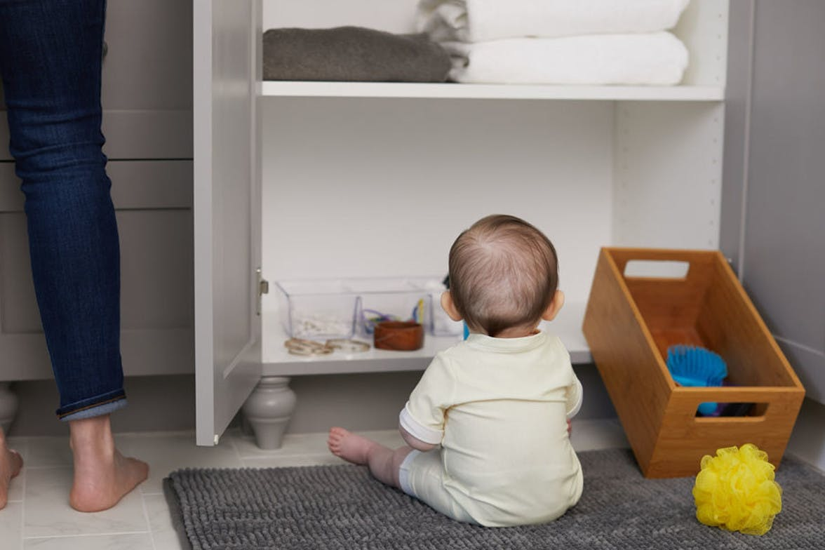 Baby sitting up and looking into an open bathroom cabinet