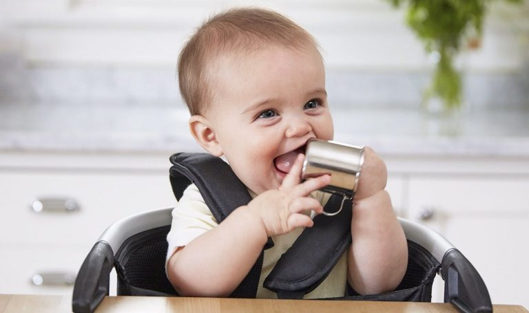 Baby sitting in a high chair holding the Drinking Cup by Lovevery
