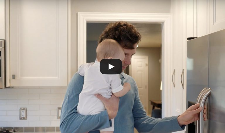 Man holding a baby about to open a refrigerator