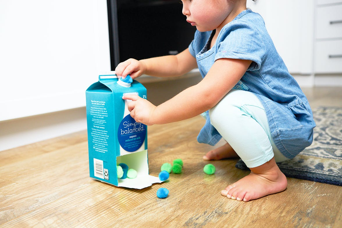 Toddler playing with a cardboard container and pom poms