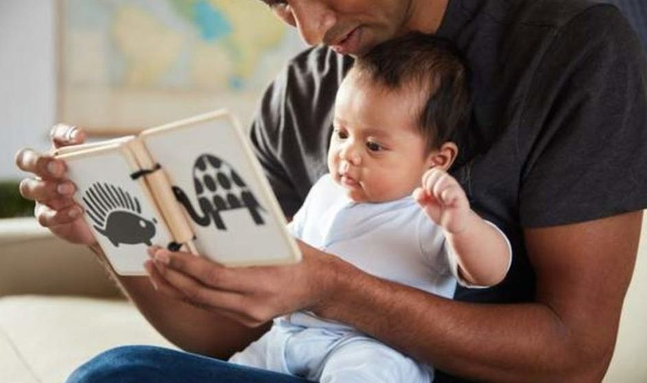 Baby sitting on man's lap looking at the Wooden Book by Lovevery