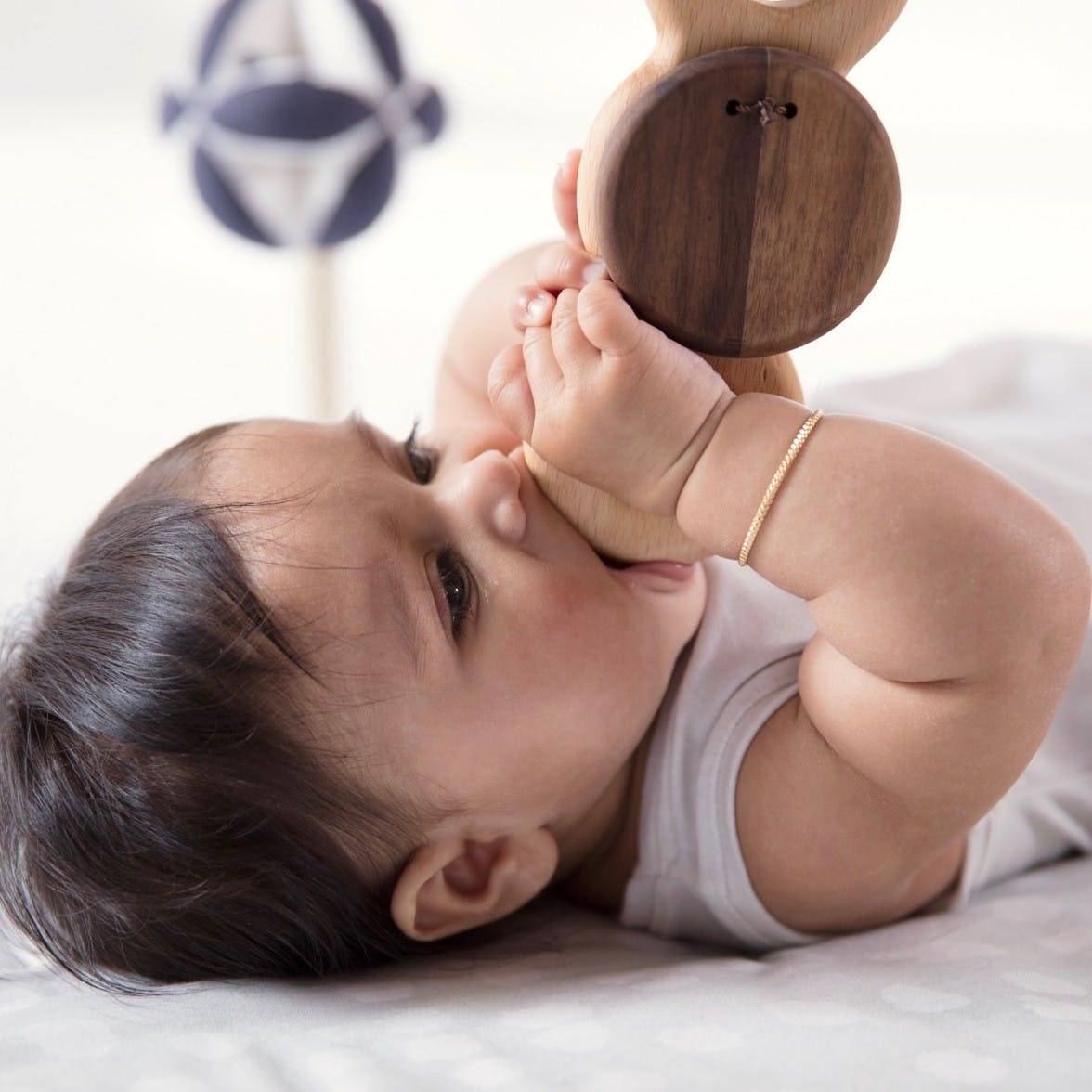 A baby laying on its back chewing on the Batting Ring from the Play Gym by Lovevery