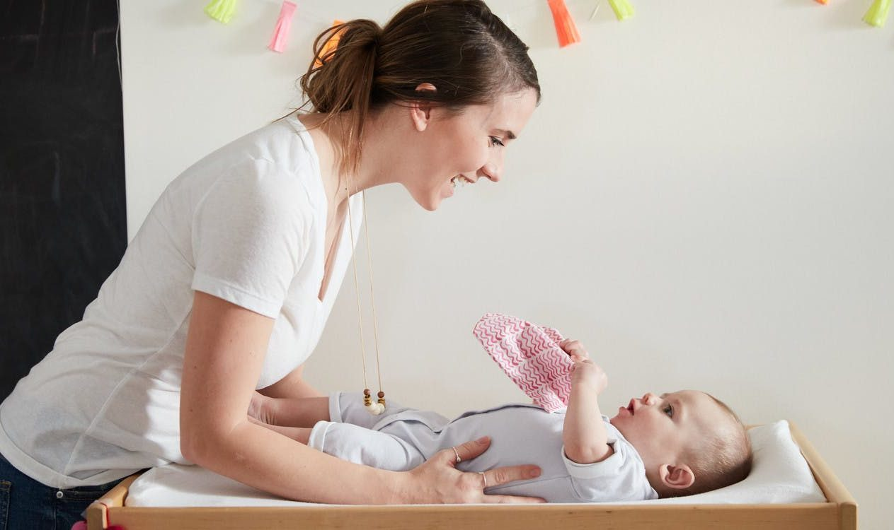 Baby on a changing table looking up at a woman