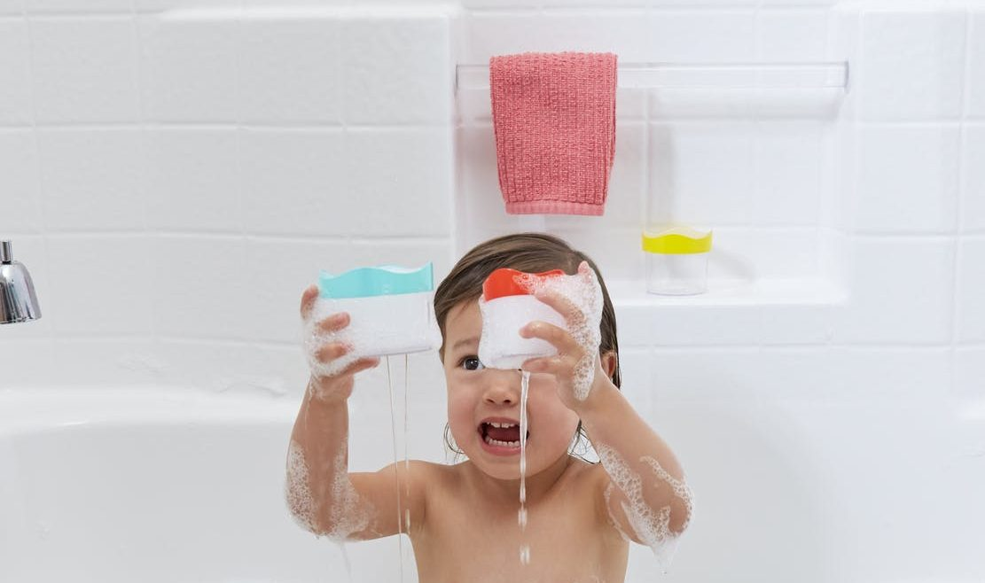 Young child in a tub playing with toys by Lovevery