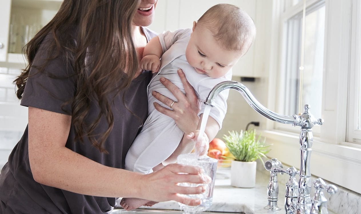 Woman holding baby while pouring water into a glass from the kitchen sink